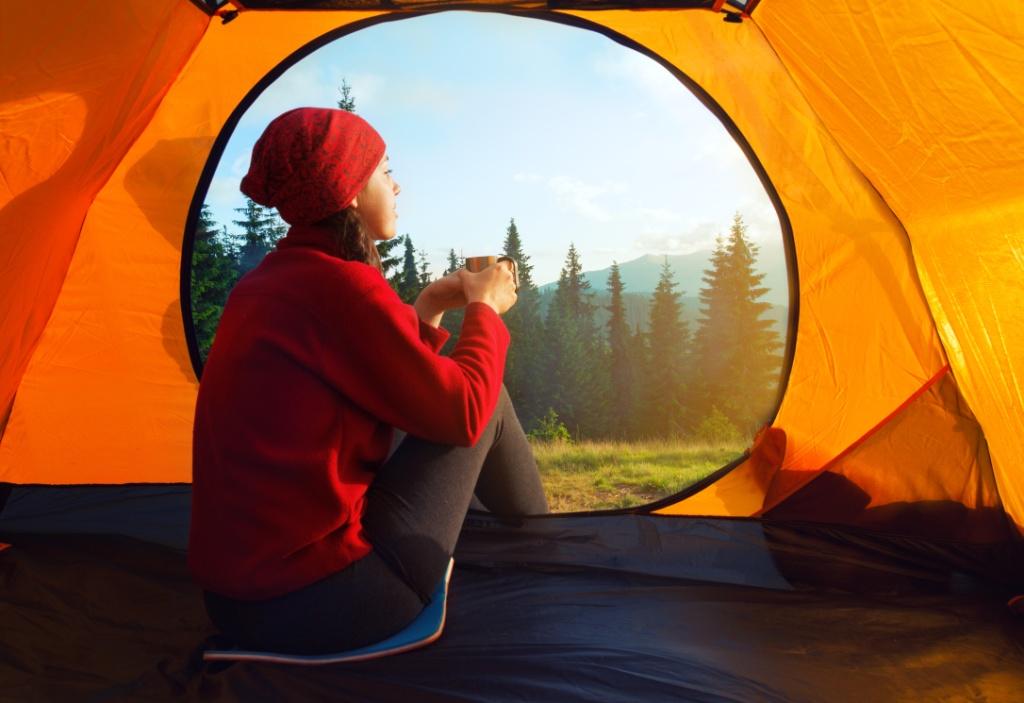 Girl sitting inside Gipfel fira tent enjoying the camp